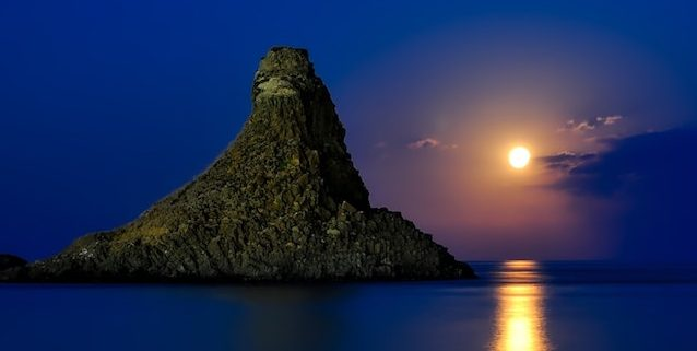 lone island with ocean backlit by hazy moon