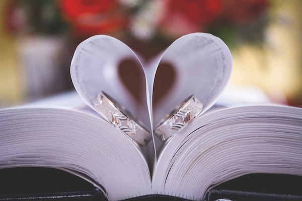 closeup of book pages with wedding bands