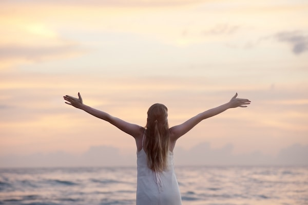 girl holding out arms at beach dawn